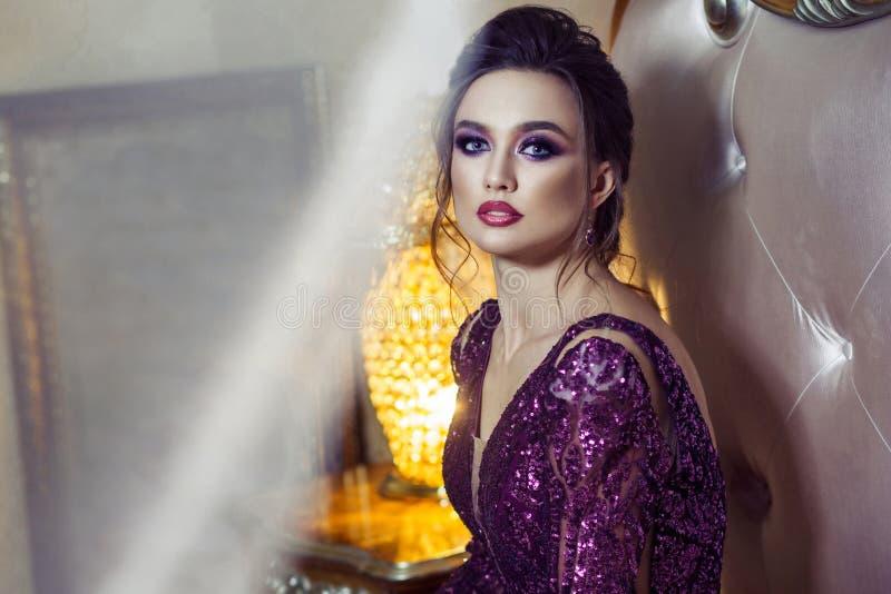 Femme attirante en égalisant la robe brillante pourpre, la coiffure et le h photo stock