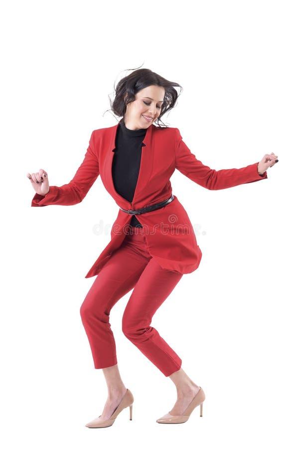 Femme attirante enthousiaste gaie d'affaires dans la danse rouge ou sauter de costume tout en célébrant photo stock