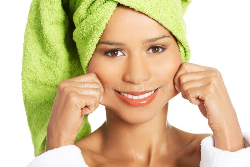 Femme attirante enveloppée en serviette, tenant sa bouche dans un sourire. images stock