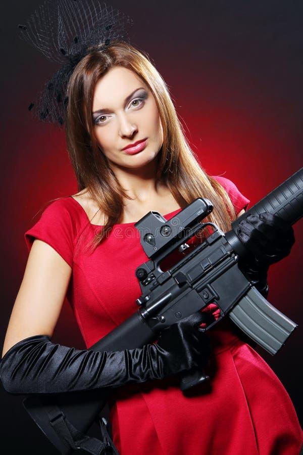 Femme attirante et sexy d'espion avec le fusil d'assaut image stock