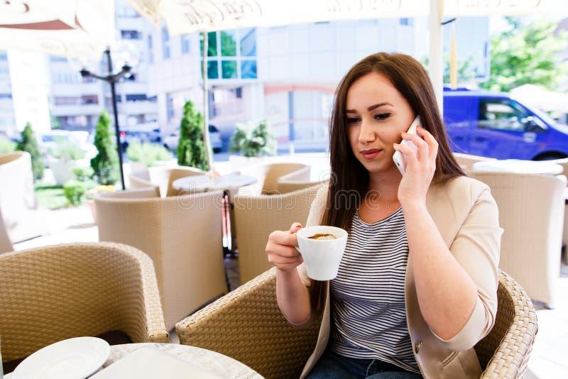 Femme attirante faisant un appel téléphonique tout en passant le temps sur la pause-café photos stock
