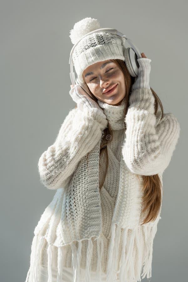 femme attirante gaie dans la musique de écoute à la mode de chandail et d'écharpe d'hiver avec des écouteurs d'isolement photo stock