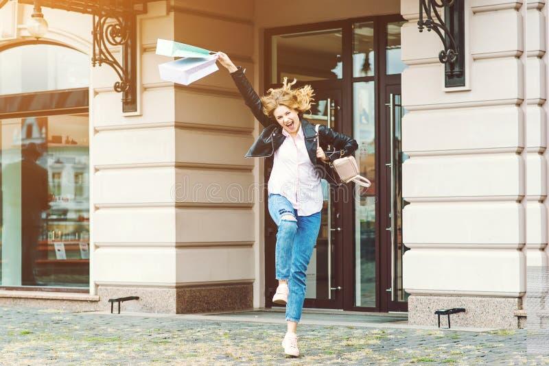 Femme attirante joyeuse sautant avec des sacs en papier après le bon achat photo libre de droits