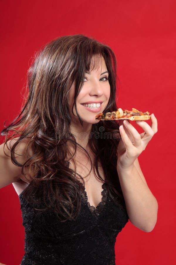 Femme attirante mangeant de la pizza image stock