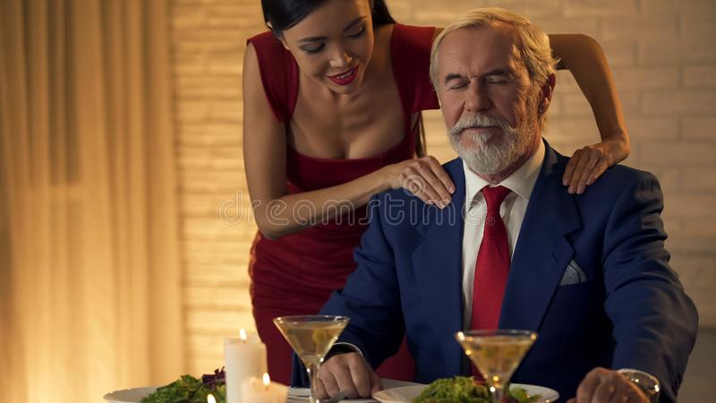 Femme attirante massant des épaules de vieil homme, proximité de couples, affection image stock