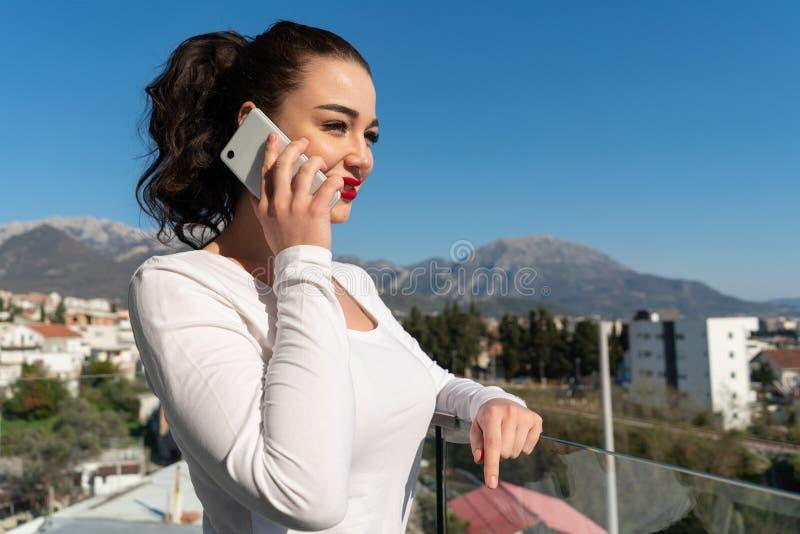 Femme attirante parlant par le t?l?phone portable sur le balcon avec la belle vue photographie stock libre de droits