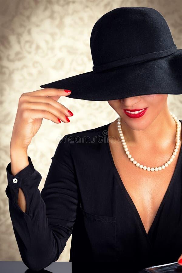 Femme attirante portant la robe, le chapeau et les perles noirs photo libre de droits