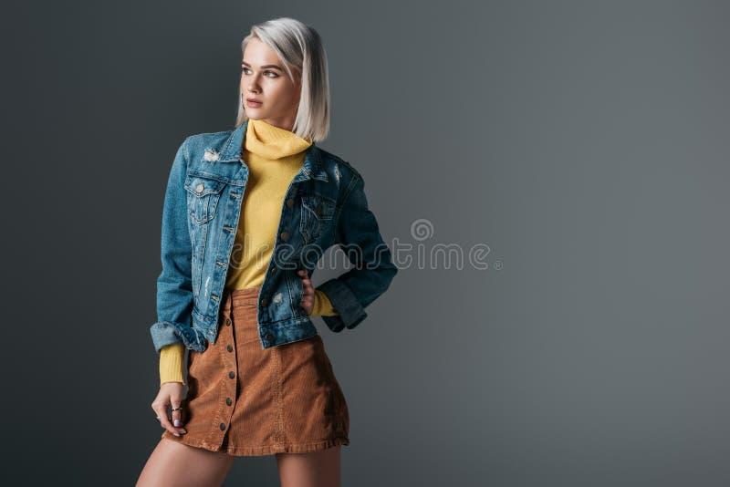 femme attirante posant dans la jupe de velours côtelé de col roulé jaune et la veste à la mode de jeans images libres de droits