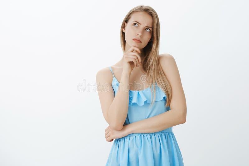 Femme attirante réfléchie intéressée et préoccupée avec les cheveux blonds dans la robe bleue fronçant les sourcils inclinant la  photos stock
