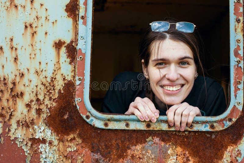 Femme attirante regardant hors de la cambuse en métal de fenêtre images stock