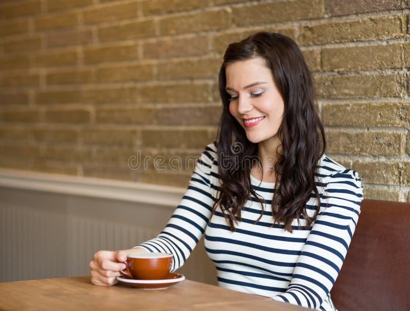 Femme attirante regardant la tasse de café en café image stock
