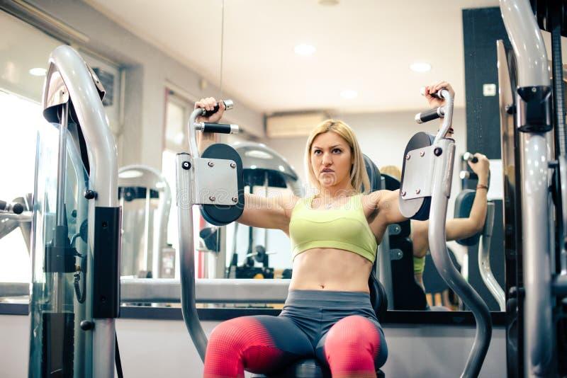 Femme attirante s'exerçant au gymnase, séance d'entraînement de bras image libre de droits