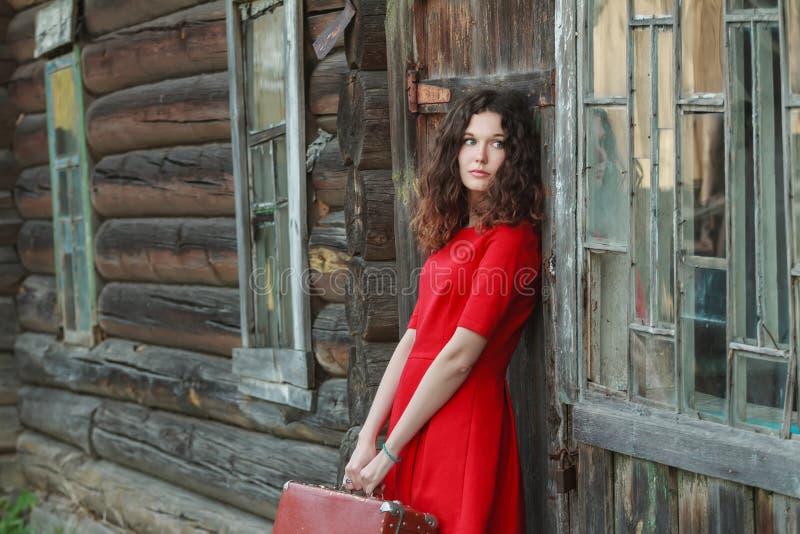 Femme attirante se penchant sur le mur en bois de la vieille carlingue de rondin avec la rétro valise images libres de droits