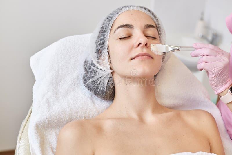 Femme attirante se trouvant sur le couh tandis que cosmetologist appliquant le masque facial sur sa peau Belle femme cherful appr image libre de droits