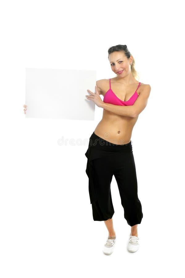 Femme attirante sexy dans le pantalon de sport et soutien-gorge de gymnase tenant la carte vierge de panneau d'affichage avec l'e image libre de droits