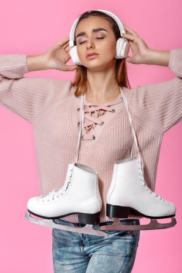 Femme attirante tenant des patins de glace photo stock