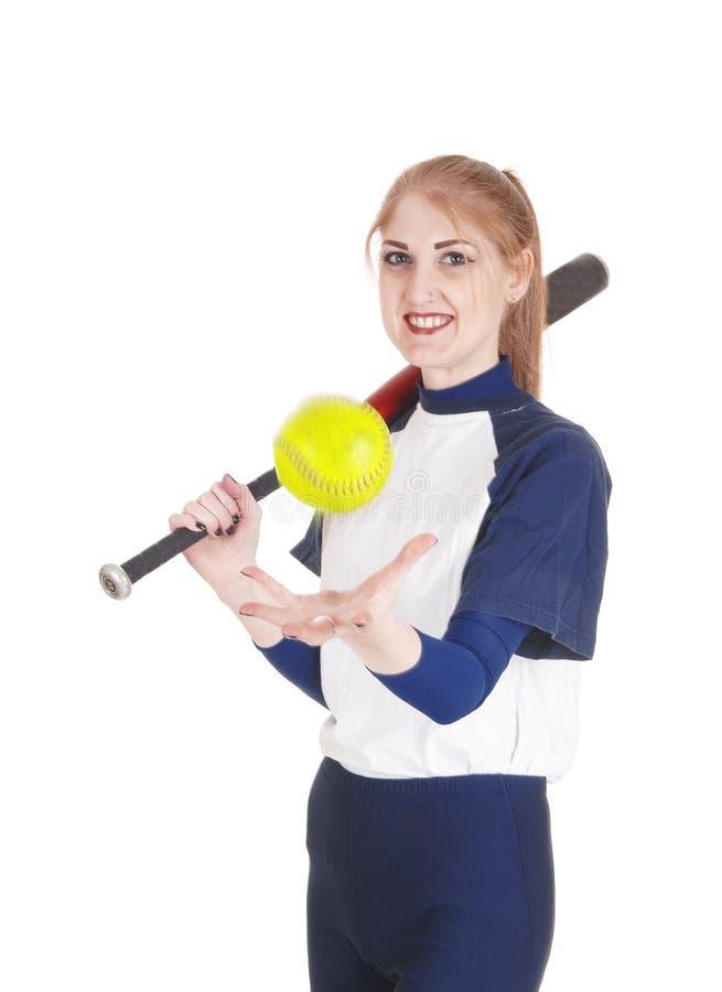 Femme attrapant le base-ball jaune photographie stock libre de droits