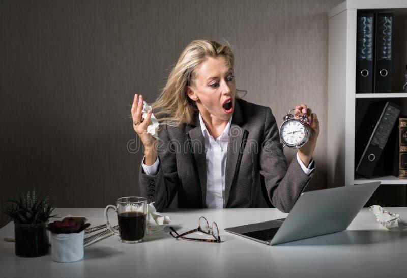 Femme au bureau dans l'effort au sujet de la date-butoir photo stock