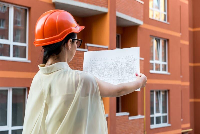 Femme au casque comparant plan et construction photos stock