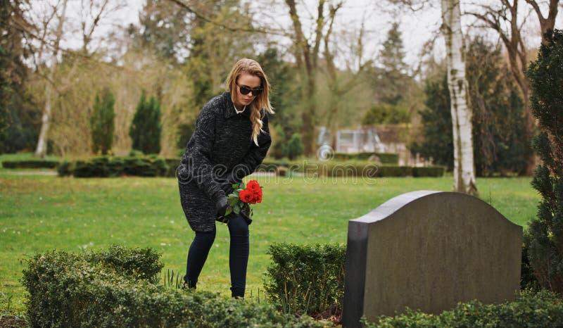 Femme au cimetière payant des respects avec les fleurs fraîches images libres de droits