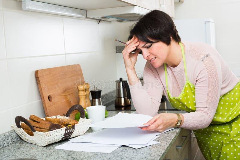 Femme au foyer âgée par milieu triste regardant par des factures images stock