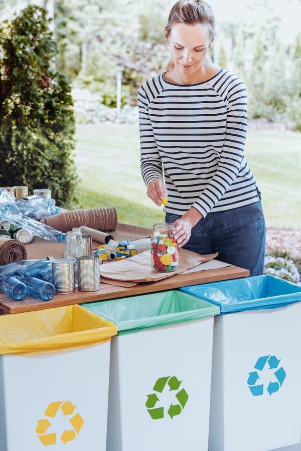 Femme au foyer assortissant les lièges colorés images stock