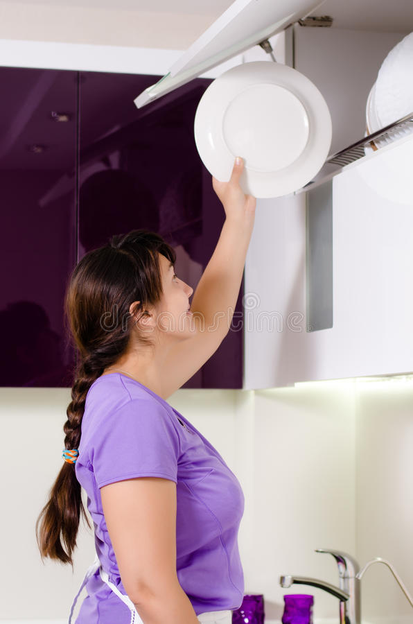 Femme au foyer attirante faisant la vaisselle image stock