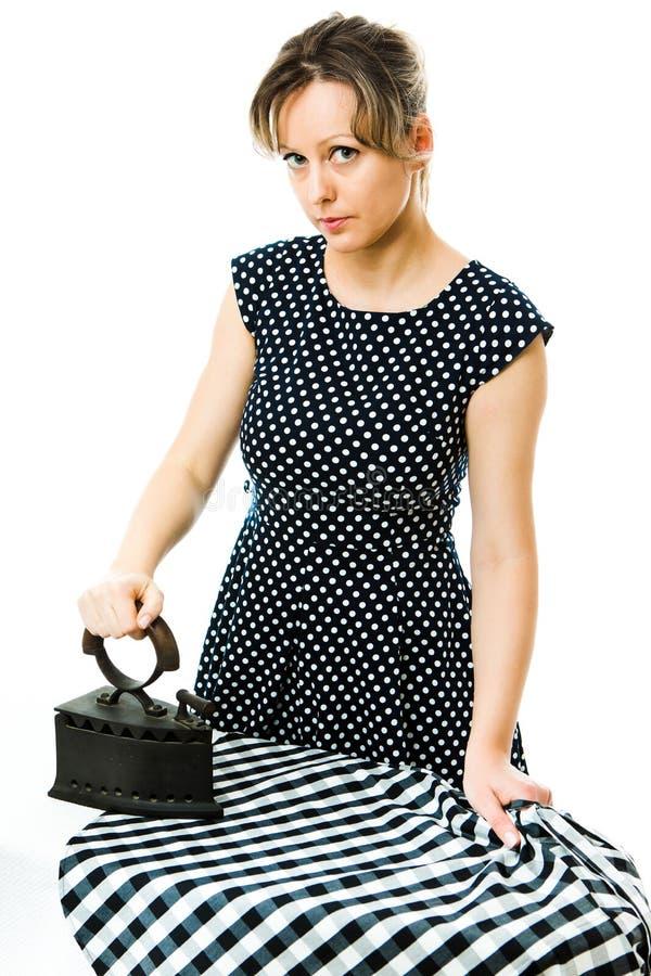 Femme au foyer attirante repassant avec l'outil repassant en métal de charbon de cru photographie stock libre de droits