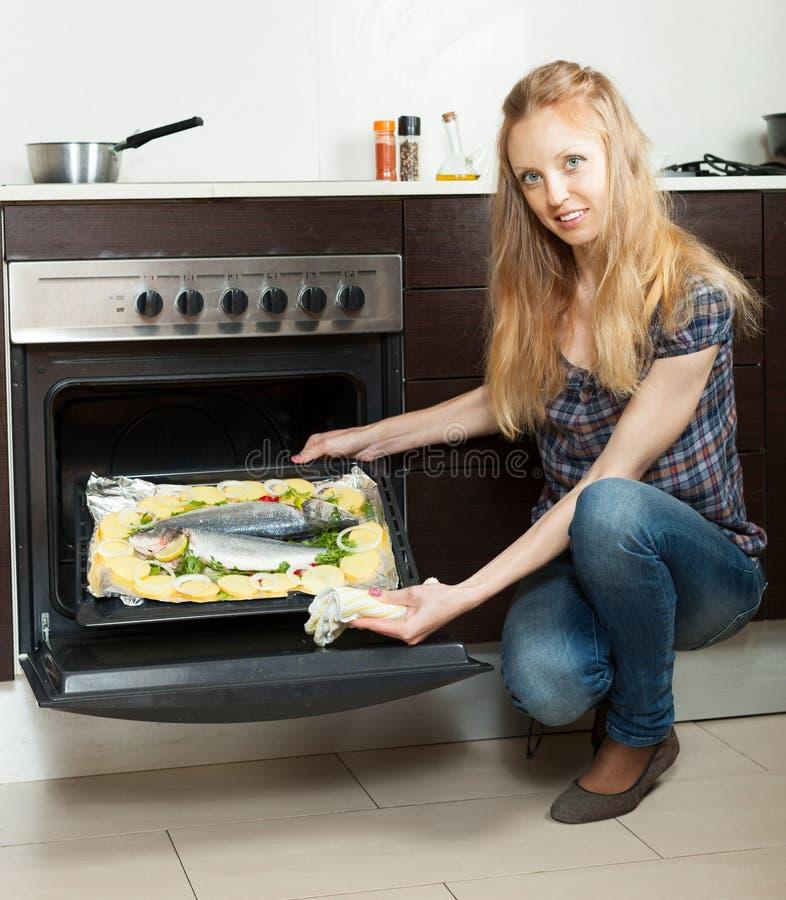 Femme au foyer aux cheveux longs faisant cuire des poissons sur la casserole de feuille en four photographie stock libre de droits