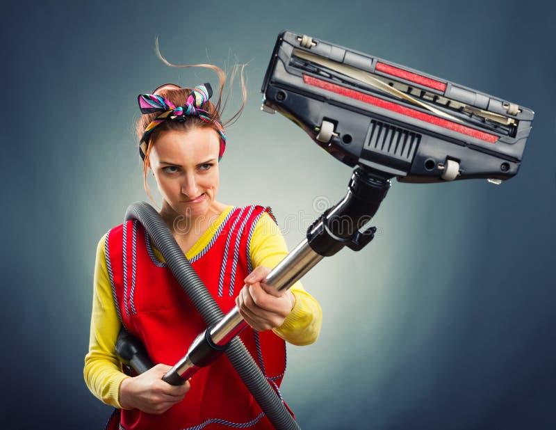 Femme au foyer avec l'aspirateur image stock