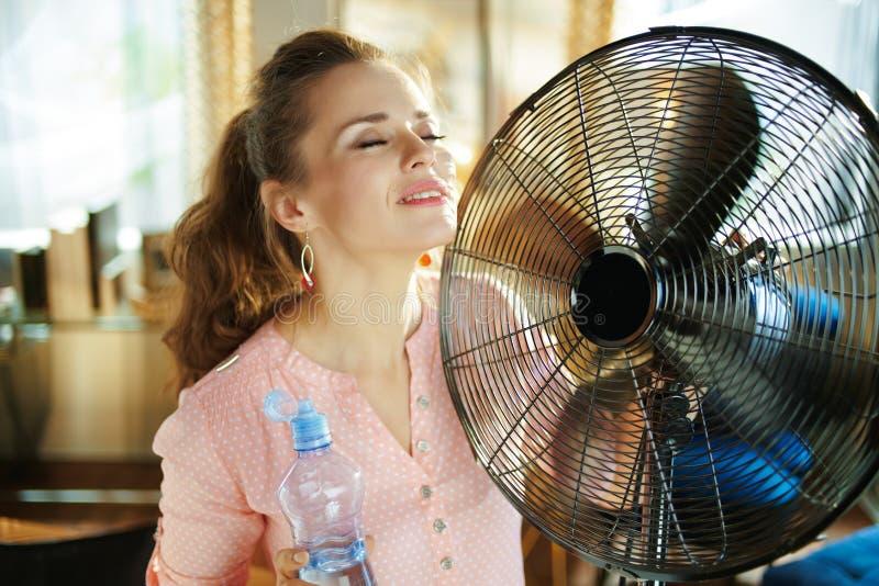 Femme au foyer avec la bouteille froide de l'eau utilisant la fan image libre de droits