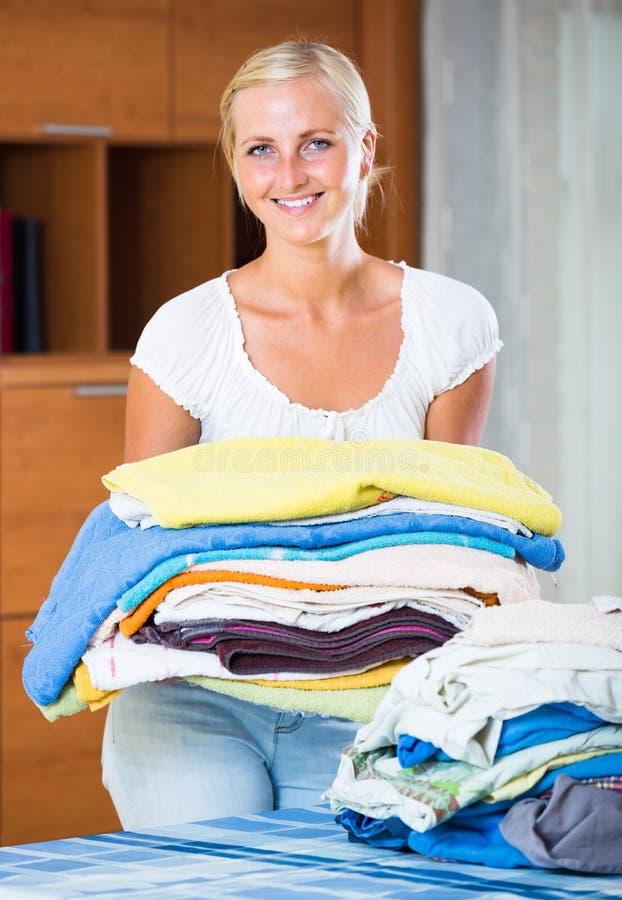 Femme au foyer avec la pile de toile photos stock