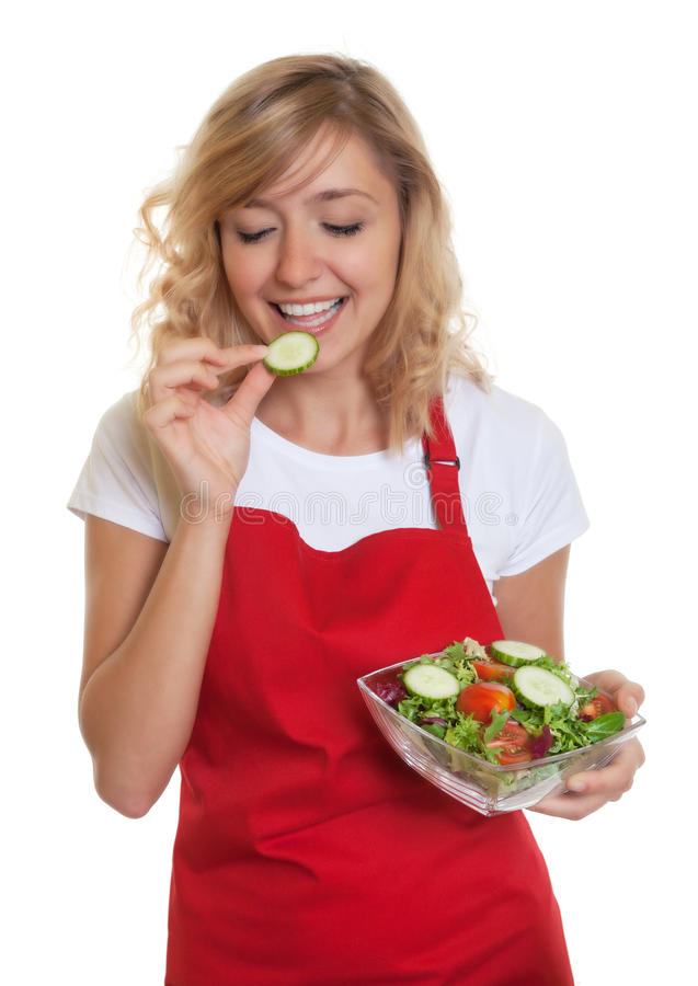Femme au foyer avec les cheveux blonds goûtant sa salade photographie stock libre de droits