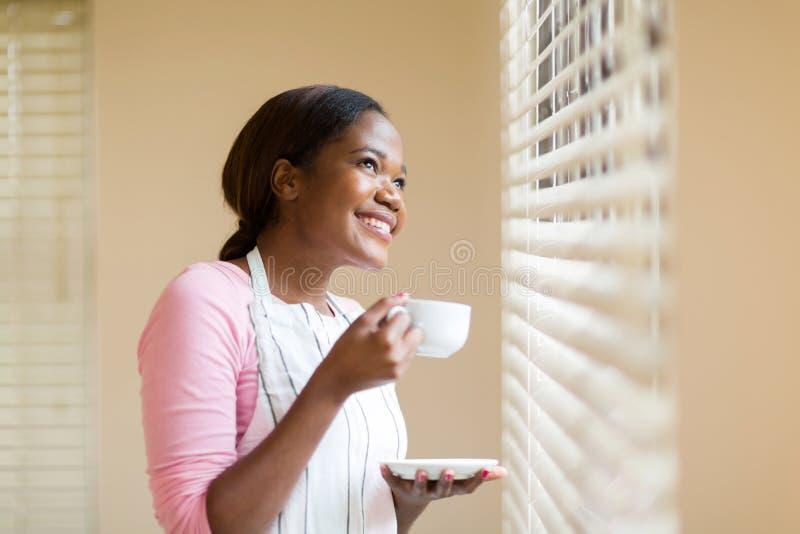 Femme au foyer ayant le café photo stock