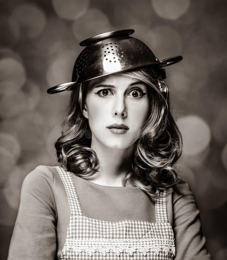 Femme au foyer blanche étonnée avec la passoire sur la tête images libres de droits