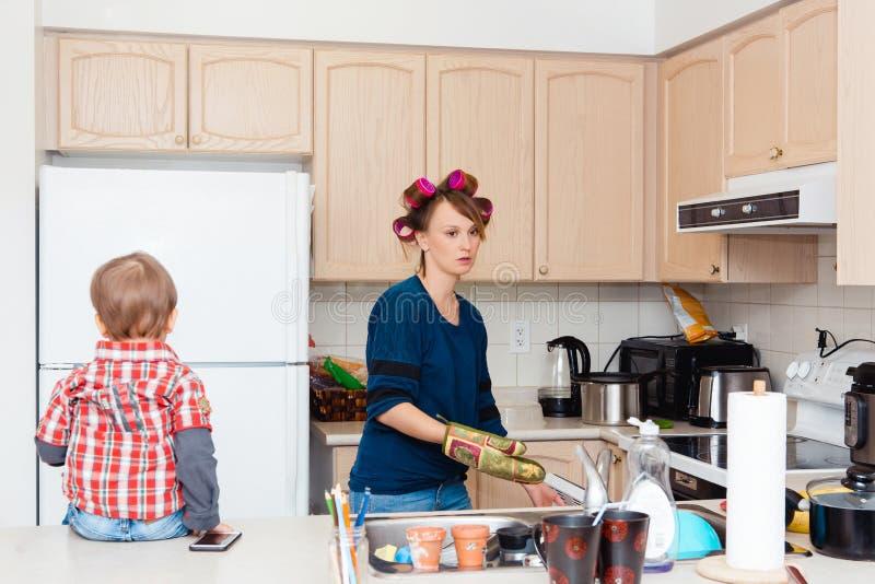 Femme au foyer caucasienne blanche occupée de mère de jeune femme avec des cheveu-bigoudis dans ses cheveux faisant cuire prépara photographie stock libre de droits
