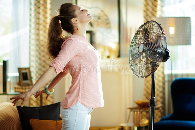 Femme au foyer d?contract?e appr?ciant la fra?cheur devant la fan fonctionnante image stock