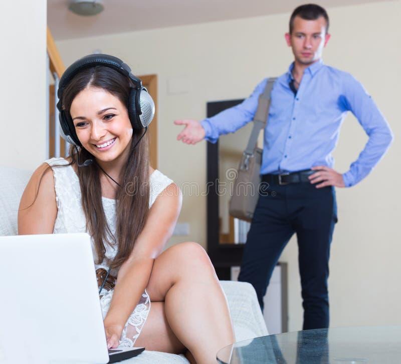 Femme au foyer dépendante à l'Internet et mari venant à la maison images libres de droits