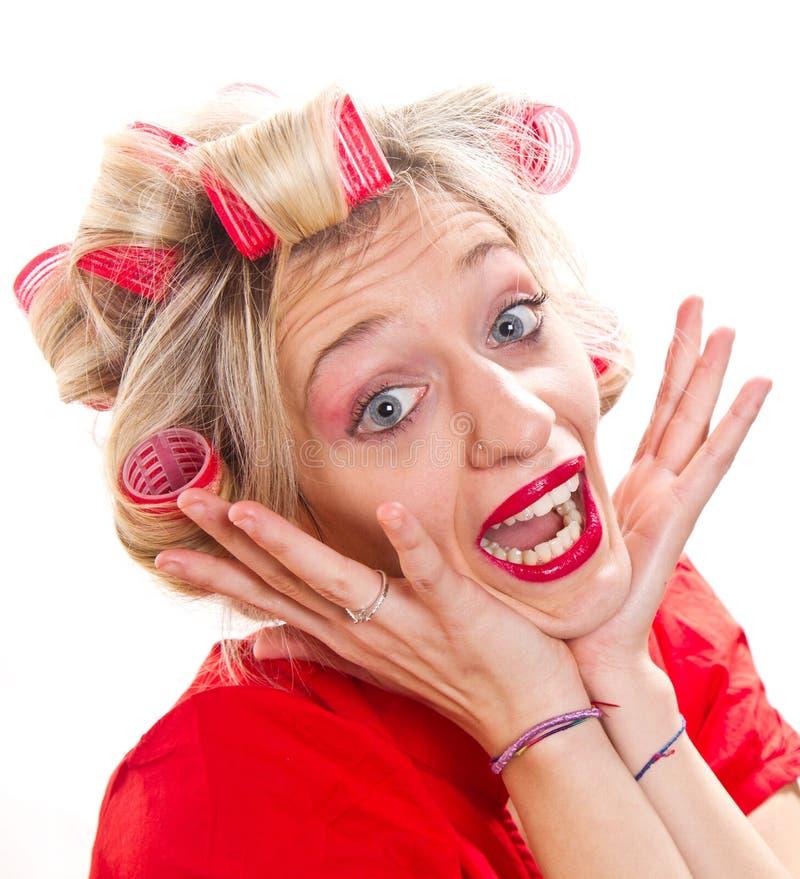 Femme au foyer désespérée avec des bigoudis de cheveux photo stock