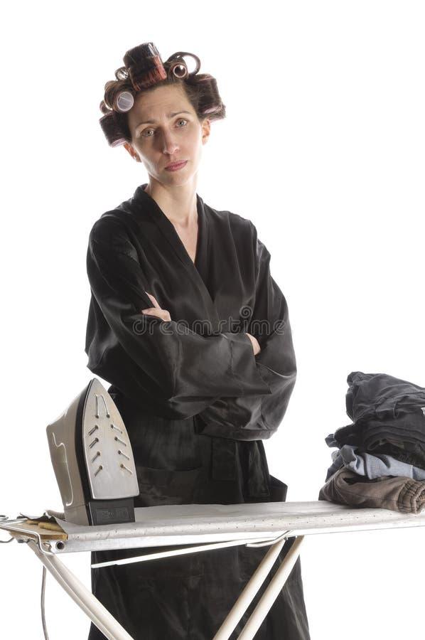 Femme au foyer désespérée repassant avec les bras croisés image stock