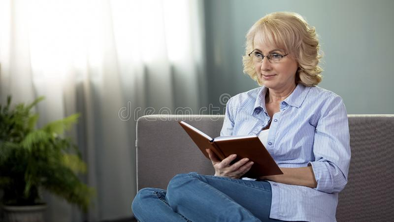Femme au foyer d'une cinquantaine d'années s'asseyant sur le sofa avec le livre, retraite de temps libre, passe-temps photographie stock