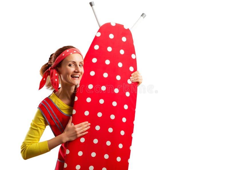 Femme au foyer de sourire avec la planche à repasser image libre de droits