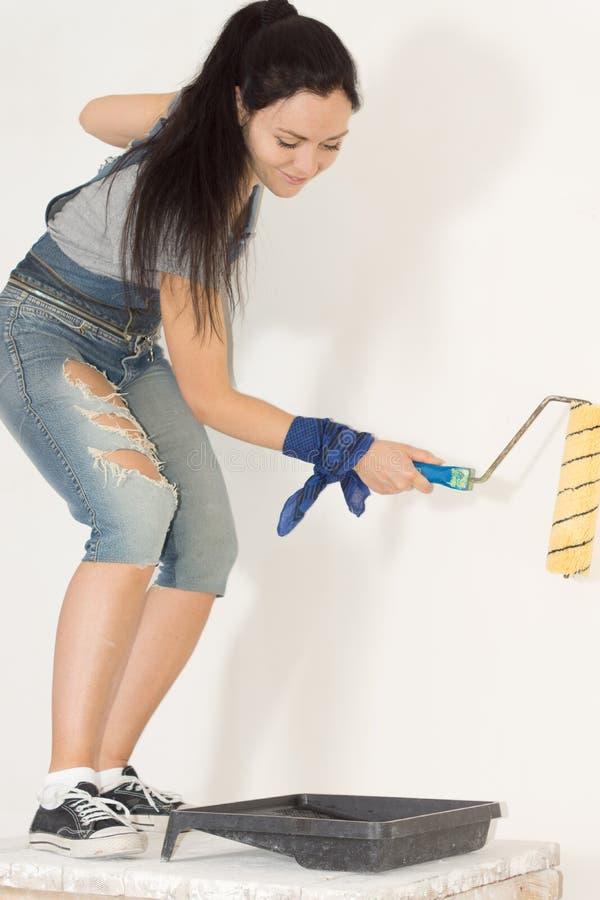 Femme au foyer de sourire peignant sa maison image stock