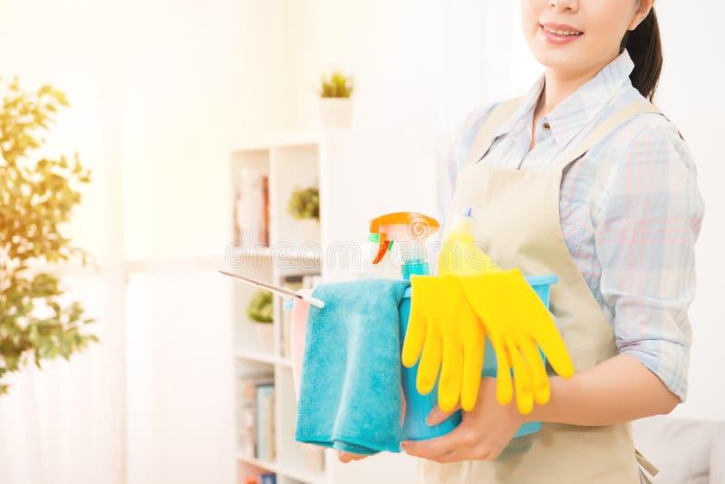 Femme au foyer de sourire tout préparée pour le nettoyage photographie stock