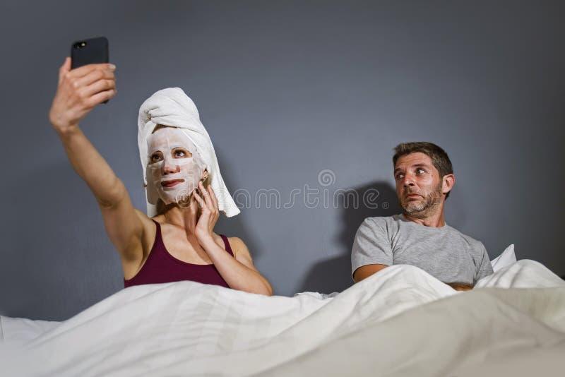 Femme au foyer excentrique avec le masque facial et la serviette de maquillage prenant le selfie dans le lit et mari avec l'expre photographie stock