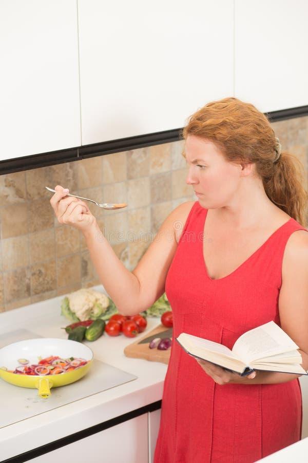 Femme au foyer faisant cuire dans la cuisine photo libre de droits