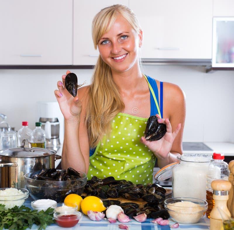 Femme au foyer faisant cuire des palourdes à la maison image stock