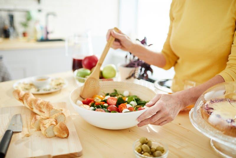 Femme au foyer faisant la salade pour le dîner photo stock