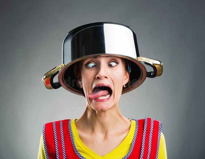 Femme au foyer folle avec la casserole de sause sur sa tête photo stock