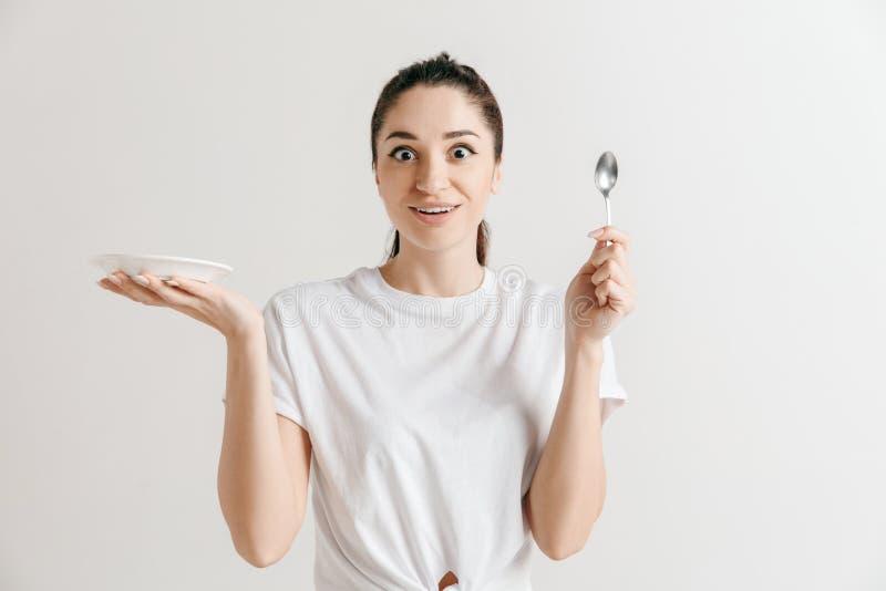 Femme au foyer folle de brune de jeune amusement avec la cuillère d'isolement sur le fond blanc image stock